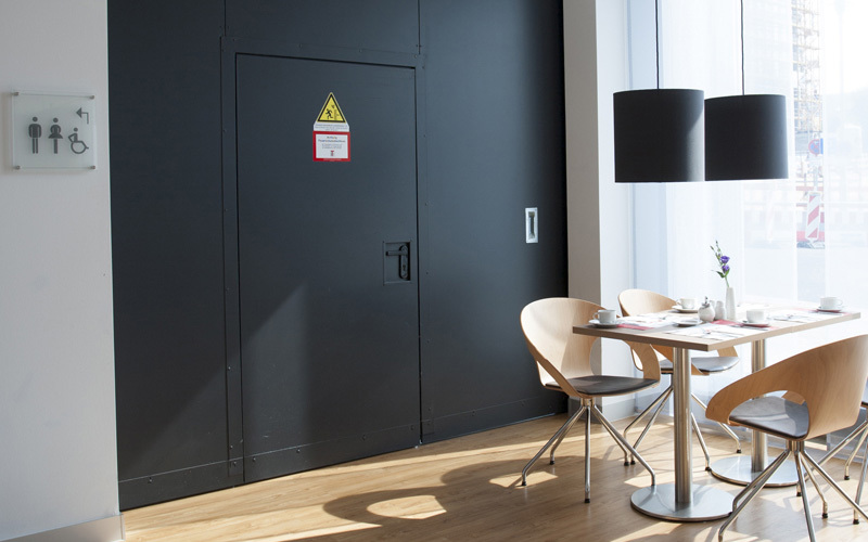 "Fire-resistant steel sliding door T90-1-FSA ""Teckentrup E"" Dividing A Hotel Space With Inset Pass Door"